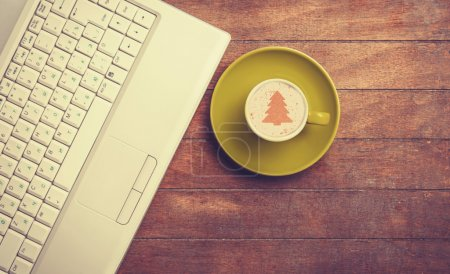 Cup of coffee and laptop on a wooden table.