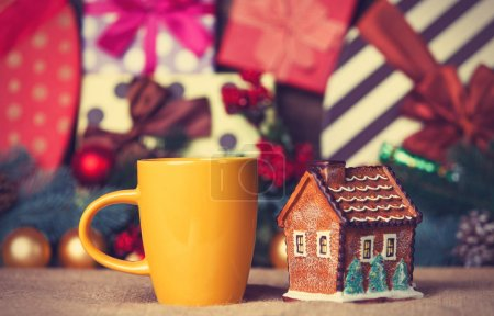 Cup of coffee and christmas house toy on a table