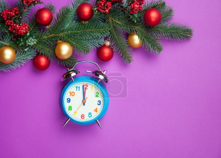 Alarm clock with pine branch on violet background.