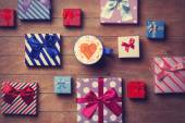 Cup and gift boxes on wooden background