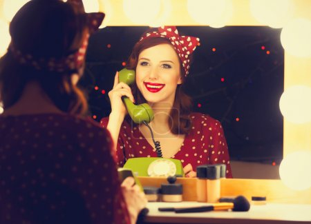 woman with dial phone applying cosmetics