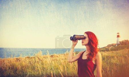 girl with binocular near Lighthouse