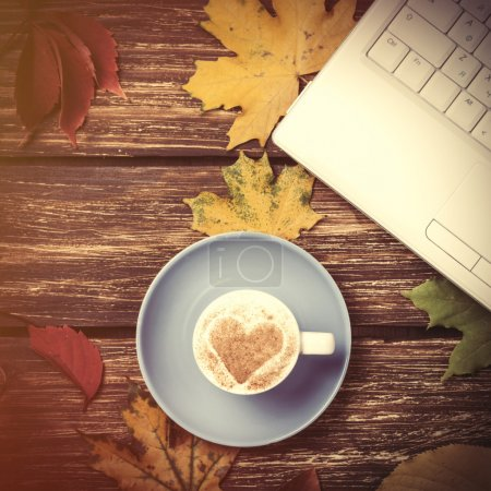 Autumn leaves, notebook and coffee cup