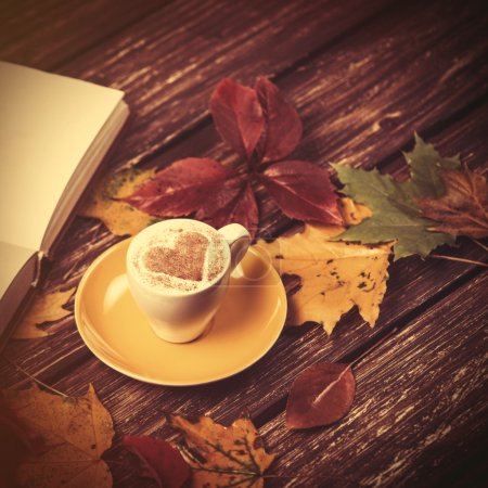 Autumn leaves, book and coffee cup