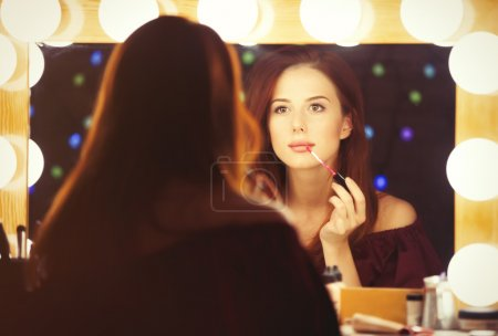 Portrait of a beautiful woman as applying makeup