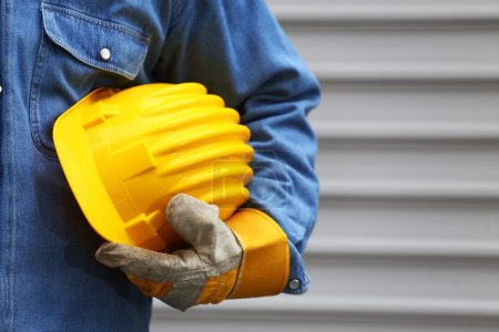 Photo for Man holding yellow helmet close up, shallow dof - Royalty Free Image