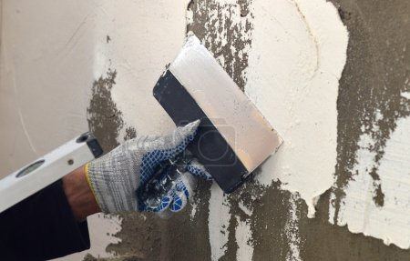 The process of applying a white putty on concrete gray wall