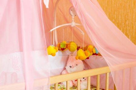 Photo pour Rond-point musical avec jouets souples, mobiles dans un berceau dans la chambre - image libre de droit