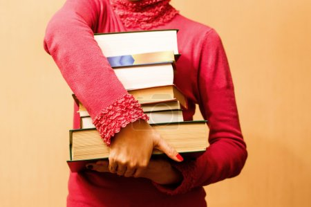 Woman in red sweater with books