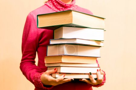Woman in red sweater with books in hand