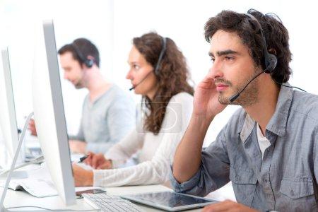 Foto de Vista de un atractivo joven trabaja en un centro de llamadas - Imagen libre de derechos