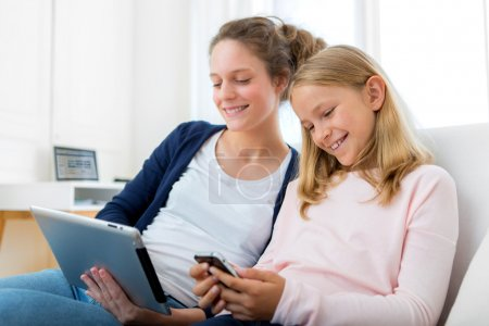 Attractive woman and little sister using tablet