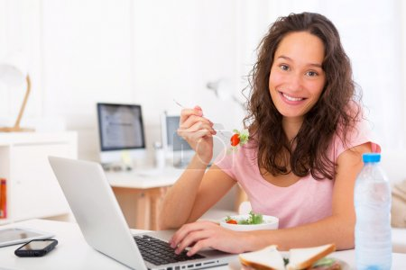 Young attractive student eating salad while working