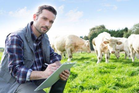 Photo pour Vue d'un jeune agriculteur attrayant travaillant dans un champ - image libre de droit