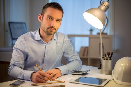 Young attractive architect working late at office