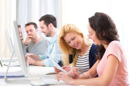 Photo pour Vue sur les jeunes gens attrayants qui travaillent ensemble au bureau - image libre de droit
