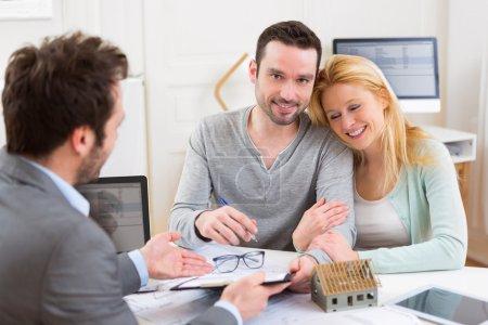 Photo pour Vue d'un jeune couple attrayant, signature du contrat avec l'agent immobilier - image libre de droit