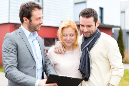Real estate agent presenting contract to young couple