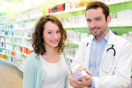 Attractive pharmacist advising a patient