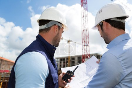Photo for View of a Engineer and worker watching blueprint on construction site - Royalty Free Image