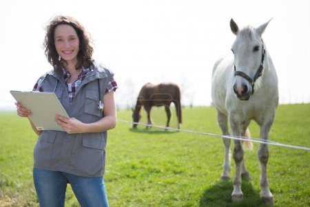 Portrait of a young attractive veterinary in fields with horse
