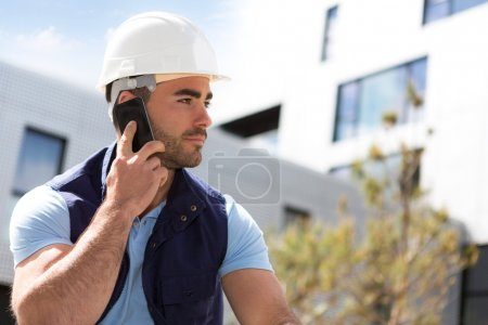 Yong attractive worker using mobile phone  on a construction sit