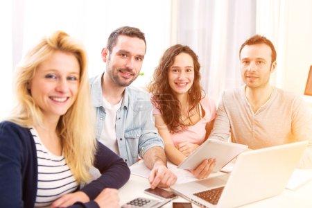 Photo pour Vue d'un groupe de 4 jeunes gens séduisants travaillant sur un ordinateur portable - image libre de droit