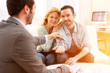 Photo pour Vue d'un agent immobilier livre les clés d'une maison neuve à un jeune couple - image libre de droit