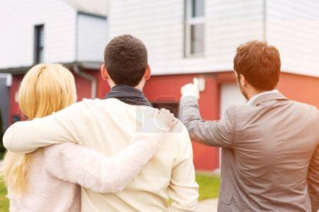Photo pour Vue d'un agent immobilier montre les détails aux clients - image libre de droit