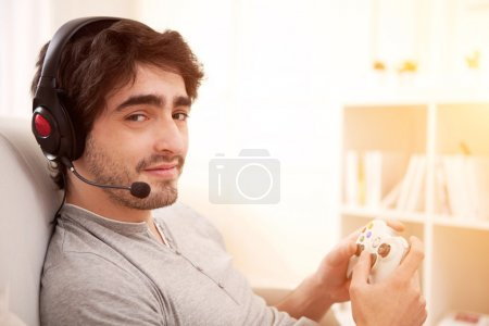 Young attractive man playing video games in a sofa
