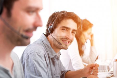 Young attractive man working in a call center