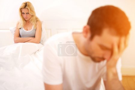 Young attractive couple having an argue in bed
