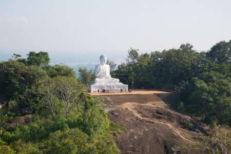View of the sculpture of sitting Buddha in the morning mist. Mihintale, Sri Lanka