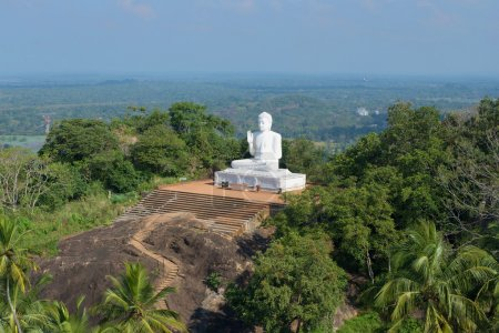 View of the sculpture of a seated Buddha from the top of mount Aradhana Gala (the Rock of Invitation). The mango plateau, Mihintale, Sri Lanka