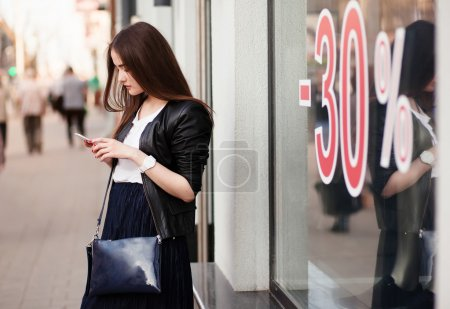 Elegant woman using a mobile phone in front of showcase boutiques. Discount from 30 percent.