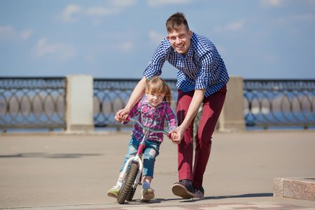 Photo for Father Teaching Daughter To Ride Bike - Royalty Free Image