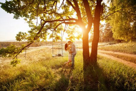 Young kissing couple under big tree with swing at sunset