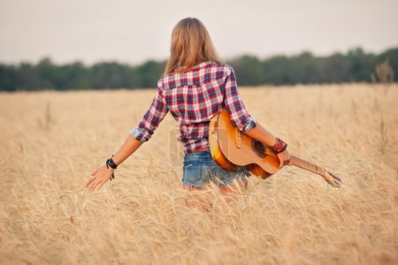 slender girl with a guitar in a wheat field.