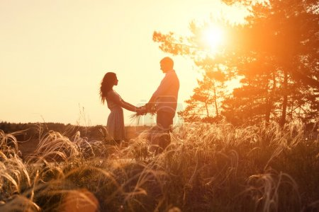 Young couple holding hands. In nature sunrise