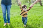Primi passi. Bambino che impara a camminare, con laiuto delle mani di madri e padri