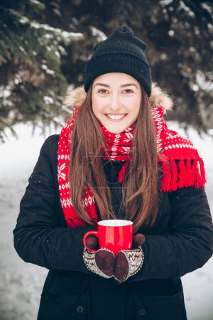 Photo for Girl drinking hot tea in the winter forest - Royalty Free Image