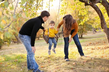 Photo for Happy family having fun on a swing ride at a garden a autumn day - Royalty Free Image