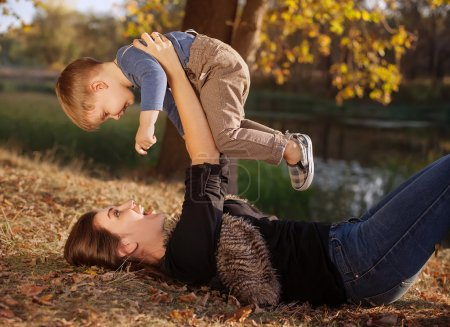 happy mother playing with her son outdoor in autumn