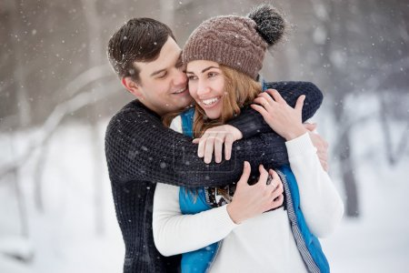 Young couple in love walking in winter park. It's snowing, winter. Young man embraces the girl. She laughs.