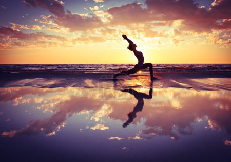 Photo for Silhouette of woman practicing yoga on the beach at sunset - Royalty Free Image