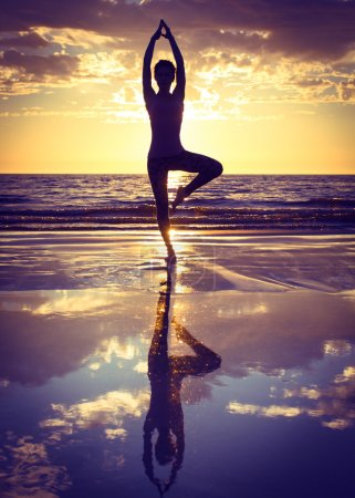 Photo pour Silhouette de femme pratiquant le yoga sur la plage au coucher du soleil - image libre de droit