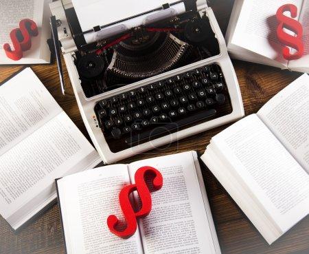 Foto de Los párrafos rojos firmen en viejos libros abiertos alrededor de la máquina de escribir retro - Imagen libre de derechos