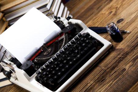 Foto de Vieja máquina de escribir retro con hoja de papel y pluma pluma y tinta sobre mostrador de madera en blanco - Imagen libre de derechos