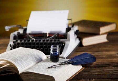 Foto de Vieja máquina de escribir retro con hoja en blanco de papel, libro abierto y tinta en el escritorio de madera - Imagen libre de derechos