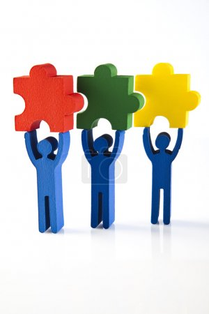 Photo for Work Concept. Figures holding colored puzzles  on white - Royalty Free Image